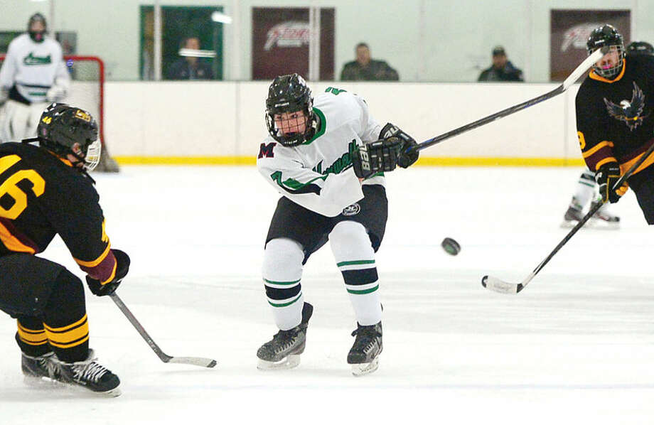 Hour photo / Erik Trautmann #2 of the Norwalk/McMahon high school co-op hockey team, Derek Lue, takes a shot against the Eastern Connecticut Eagles at the SoNo Ice House Saturday.