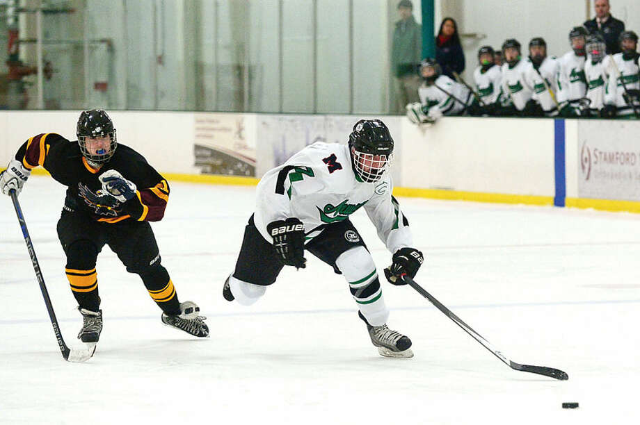 Hour photo / Erik Trautmann #17 of the Norwalk/McMahon high school co-op hockey team, Jake Flewellyn, moves past the Eastern Connecticut Eagles at the SoNo Ice House Saturday.