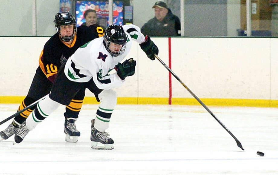 Hour photo / Erik Trautmann The Norwalk/McMahon high school co-op hockey team battles the Eastern Connecticut Eagles at the SoNo Ice House Saturday.