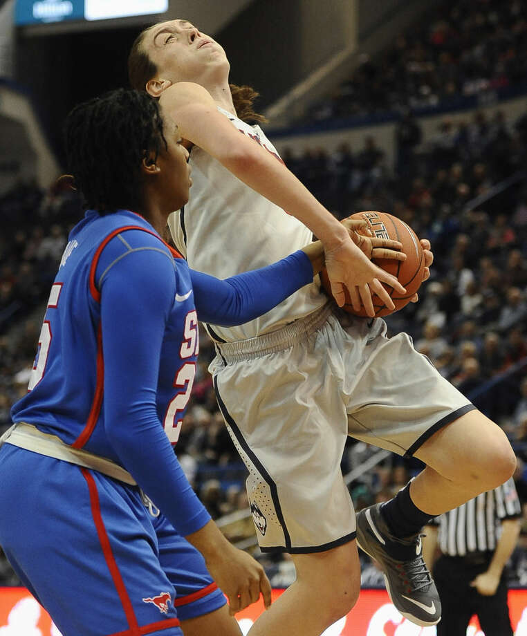 SMU's Taylor Brame, left, fouls Connecticut's Breanna Stewart, right, during the first half of an NCAA college basketball game, Saturday, Dec. 27, 2014, in Hartford, Conn. (AP Photo/Jessica Hill)