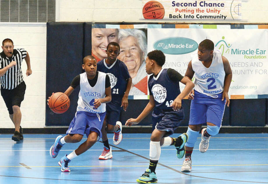Hour photo / Erik TrautmannJamal Boyd for TMT (Teaching Mentoring Training) dribbles up court in their game against King's Kids during the Listening Ear Holiday Classic Basketball Tournament Saturday at Ben Franklin School. Champioships will be held Sunday at Brien McMahon High School.
