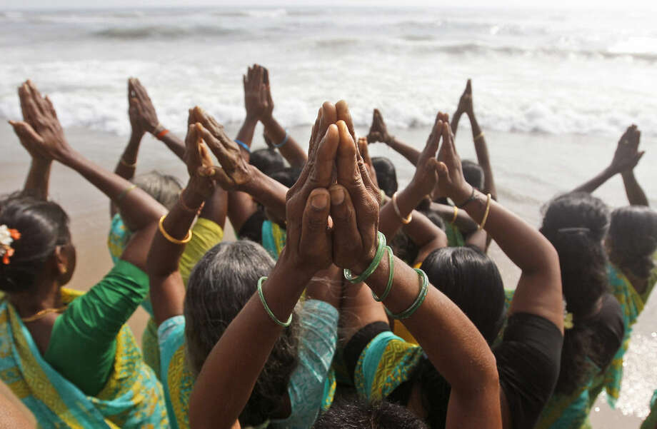 Indian women offer prayers on the Marina Beach at the Bay of Bengal to commemorate the 10th anniversary of the 2004 Tsunami in Chennai, India, Friday, Dec. 26, 2014. Crying onlookers took part in beachside memorials and religious services across Asia on Friday to mark the 10th anniversary of the Indian Ocean tsunami that left more than a quarter million people dead in one of modern history's worst natural disasters. (AP Photo/Arun Sankar K)