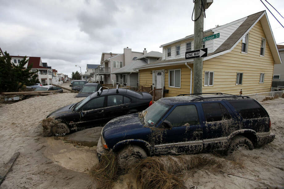FILE - In this Oct. 30, 2012 file photo, cars lifted by floodwater are mired in several feet of sand in the aftermath of Superstorm Sandy, in Long Beach, N.Y. Lawyers representing about 1,500 homeowners are trying to prove that some engineering firms hired to inspect the damage issued bogus reports to give skeptical insurers ammunition to deny claims. (AP Photo/Jason DeCrow, File)