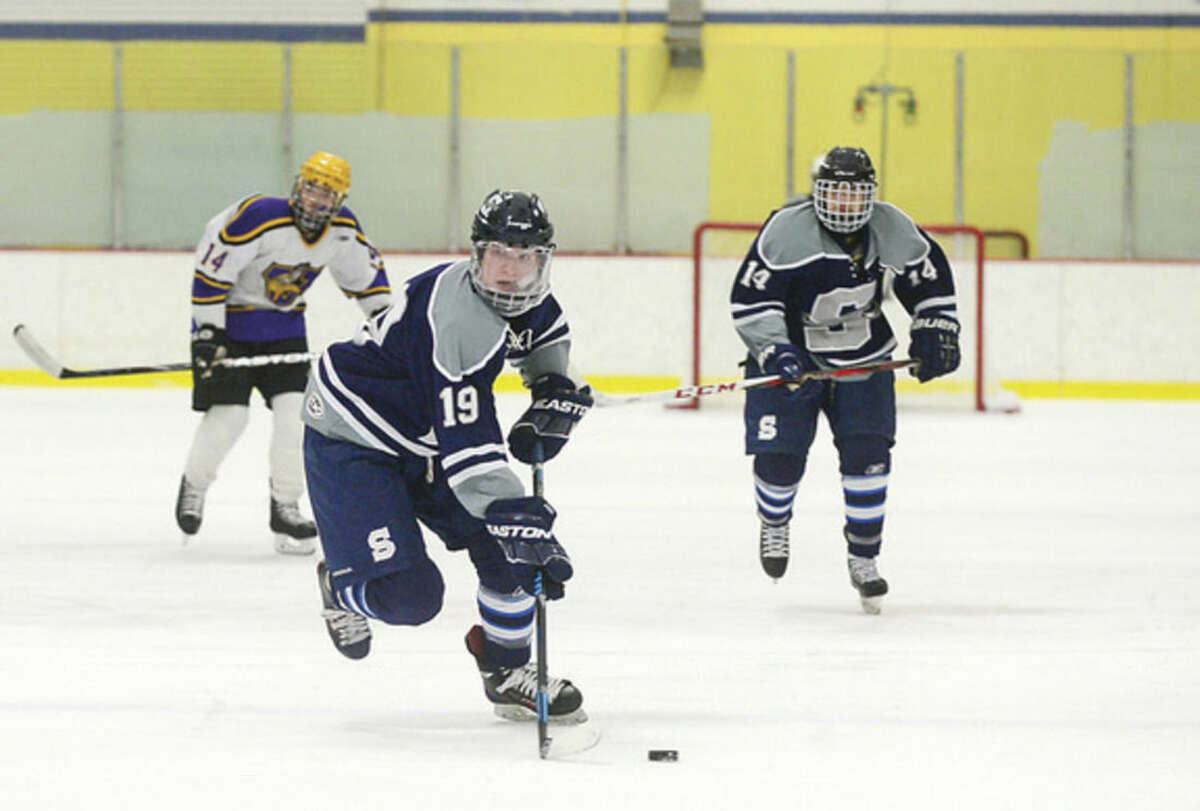 Hour photo/Erik Trautmann Staples High Schoo's Samuel Hew carries the puck during Saturday's game againstWesthill at Terry Connors Rink in Stamford.