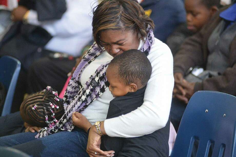 Hour Photo/Alex von Kleydorff Carolyn Bush holds her son and daughter Hayes and Chyna on her lap during the Martin Luther King Jr. Annual March and Program at The Yearwood Center in Stamford monday