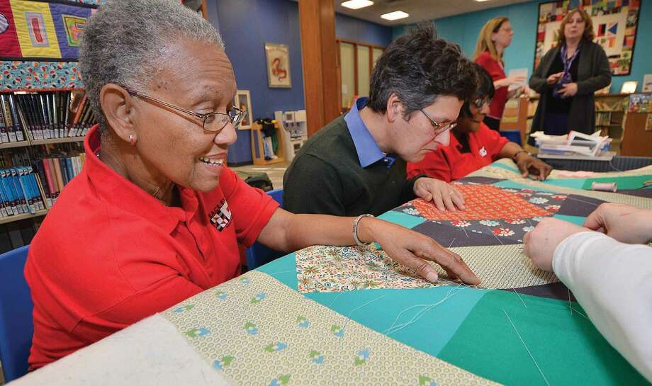 Hour Photo/Alex von Kleydorff Dorothy Byrd helps the Peace by Piece group work on the next quilt