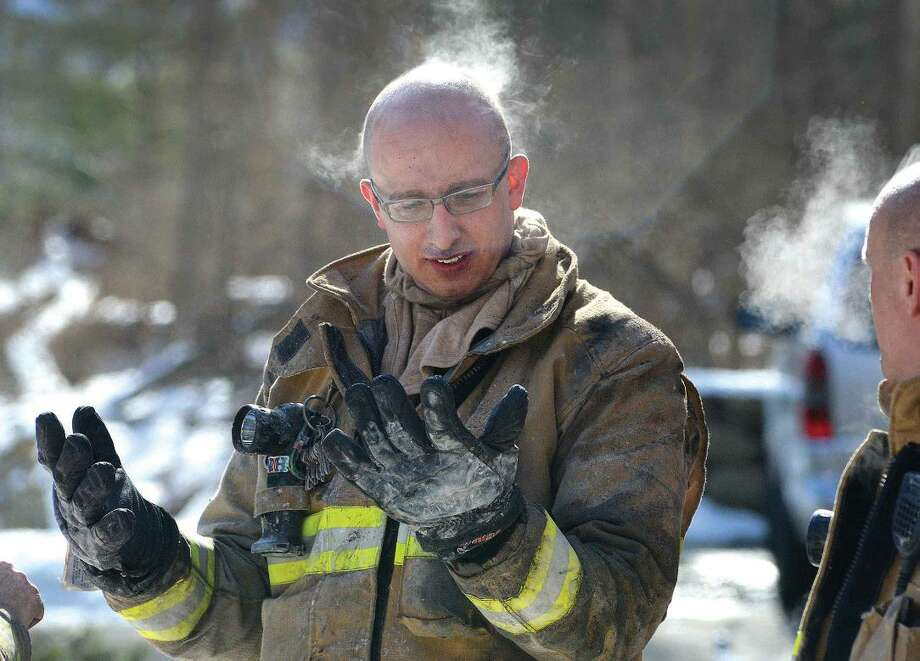 Hour Photo/Alex von Kleydorff Wilton Firefighter Mike Blatchley check his equipment as frigid temperatures cause steam to rise from his head after removing his helmet during a house fire in Wilton on Tuesday