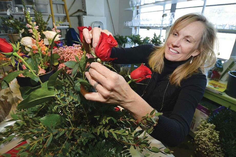 Hour Photo/Alex von Kleydorff Jan Peterson, Owner of Stewart Flowers in Wilton Center Puts the final touches on a bouquet of Long Stem Red Roses for a Valentines Day customer. Friday is one of the biggest days for Florists along with Mothers day, but the Wilton shop which has been serving the area for 50 years is ready for the flood of orders over the next few days.