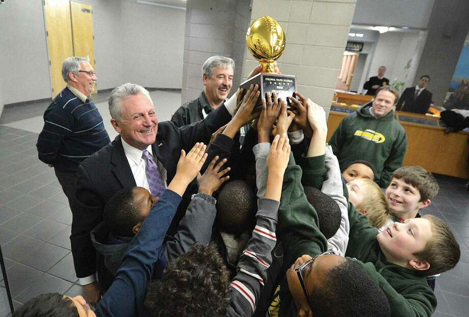 Hour Photo/Alex von Kleydorff Mayor Harry Rilling helps The Norwalk Packers hoist their Colonial State Champions trophy in the air before he puts it in the trophy case at City Hall