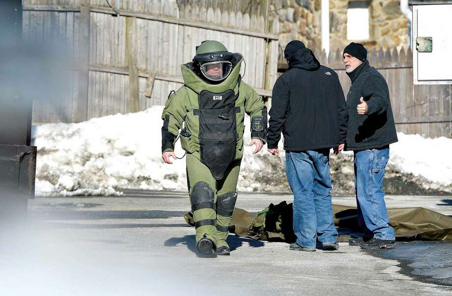 Hour Photo/Alex von Kleydorff. A member of the Stamford Bomb Squad suits up and enters Puppies of Westport on Thursday afternoon to investigate a suspicious cell phone that was left on the counter by a man wearing lipsick