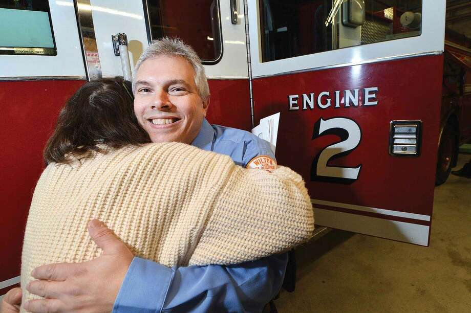 Hour Photo/Alex von Kleydorff Wilton Firefighter Tom Coon gets a hug from Fire Department Administrator Kathy Horn as she wishes him well on his retirement after 33 years of service with the department.
