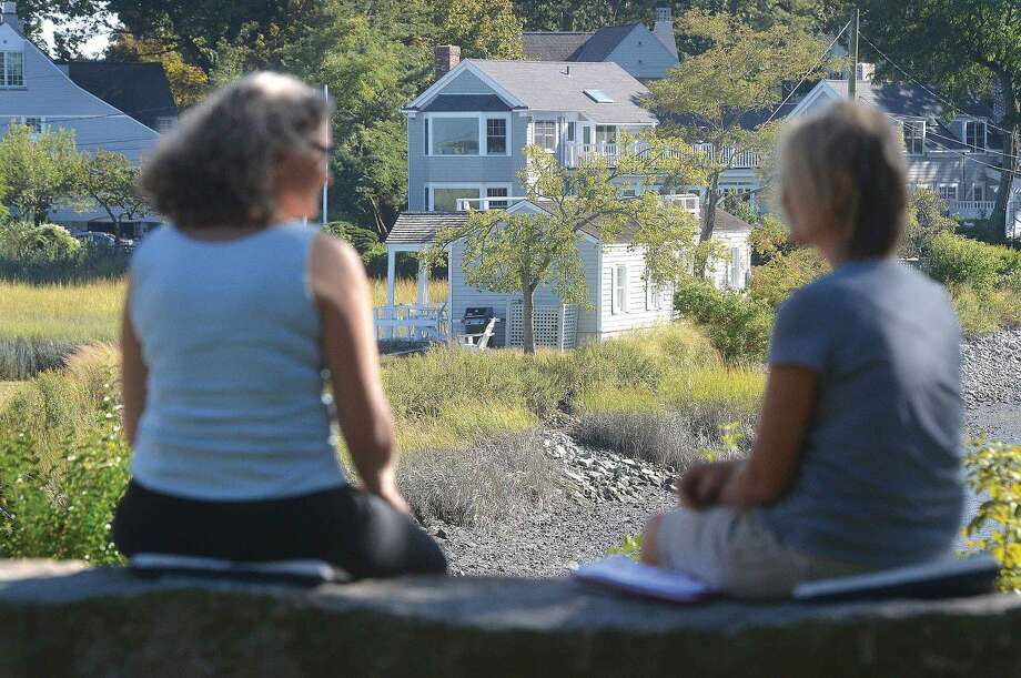 Hour Photo/Alex von Kleydorff. People sit on a stone bench at farm Creek nature Preserve that looks over the property at 2 Nearwater rd