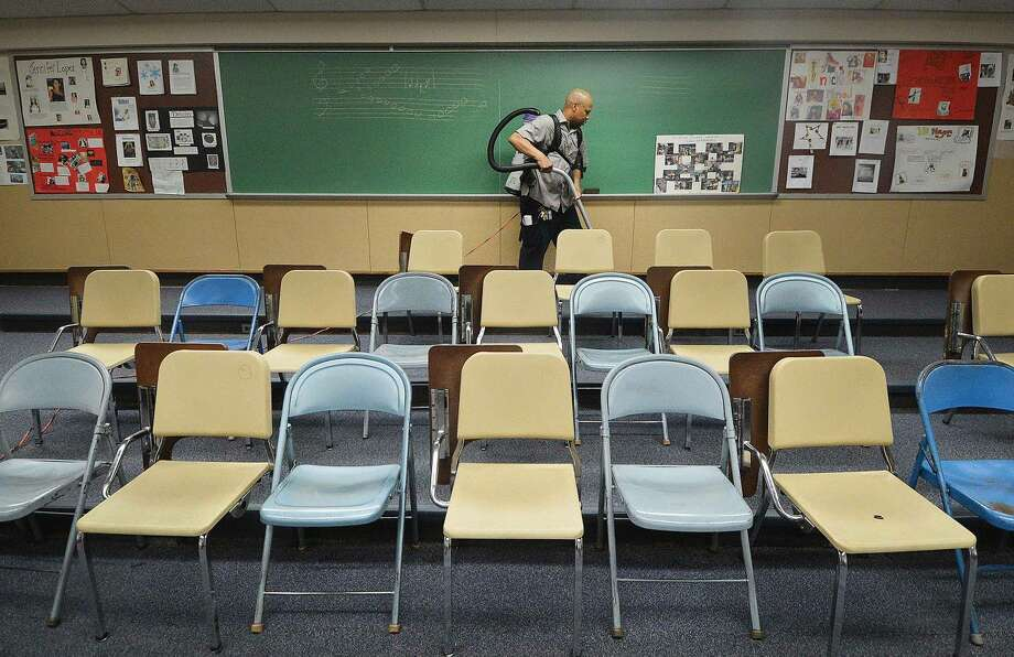 Hour Photo/Alex von Kleydorff Custodian Danny Thorne cleans around the many chairs in the music room at Nathan Hale School, one of the bigger rooms he is responsible for incuding the biggest, the Cafeteria