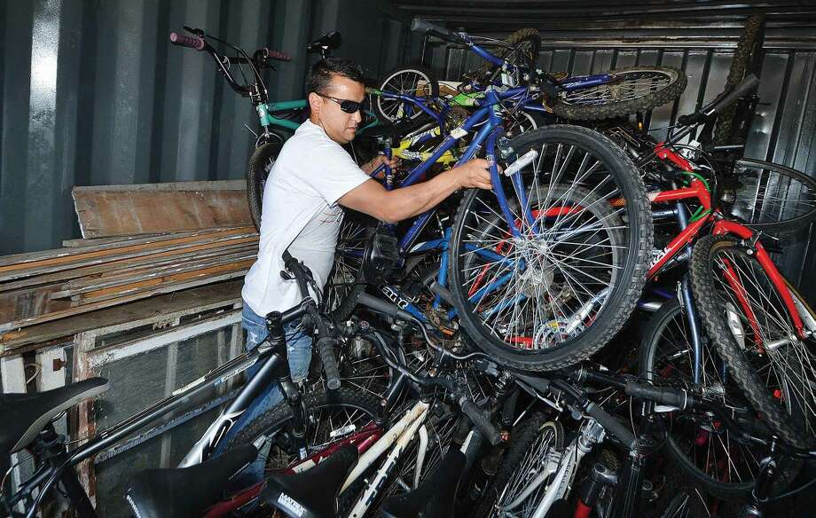 Hour Photo/Alex von Kleydorff Two Wheels Co-Founder Hector Correa stackes the donated bikes into a storage trailer at King Industries until they can be made ready for kids