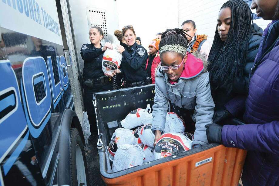 Hour Photo/Alex von Kleydorff The Stamford Police Association donates 55 turkeys to the Food Bank of Lower Fairfield County and delivers them with the help of the members of the SPA's Girls Leadership Program.