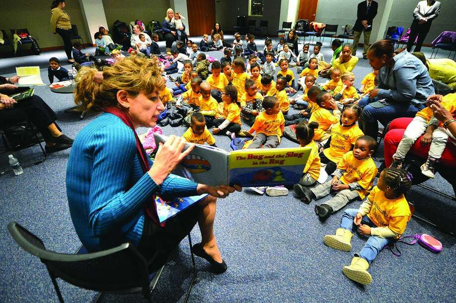 Hour Photo/Alex von Kleydorff UCONN President Susan Herbst reads 'The Bug, The slug in the Rug' to kids during its annual reading day at The Stamford Branch at UCONN
