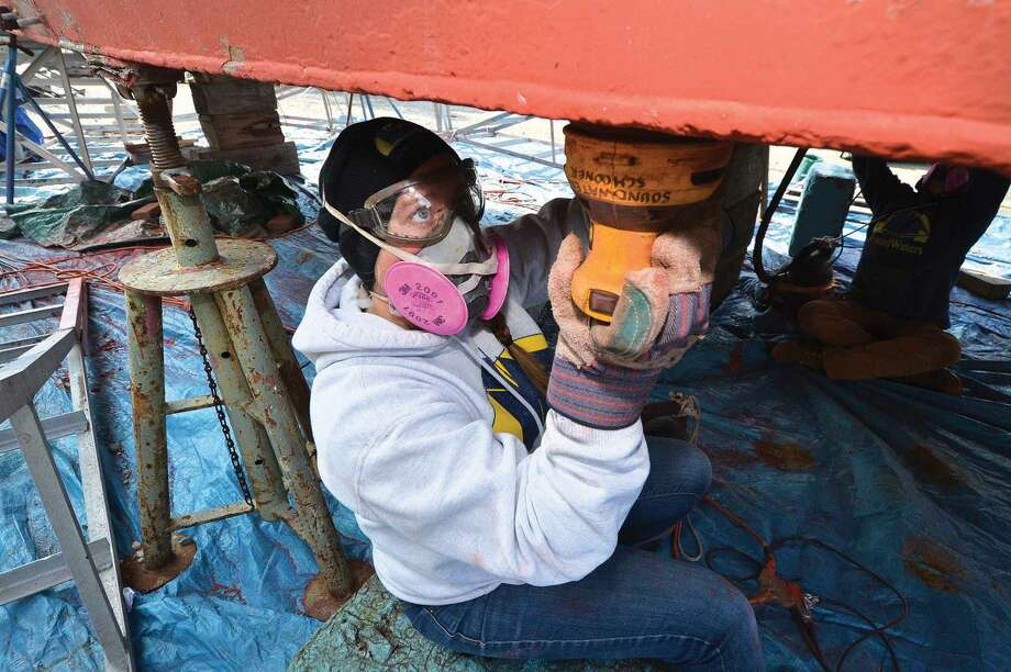Hour Photo/Alex von Kleydorff Deckhand Educator Sage Donpineo helps the crew sand the old paint off the underside of the Schooner SoundWaters, in order to get a fresh coat on while the boat is up for repairs and maintenance over the winter at Cove Marina in Norwalk