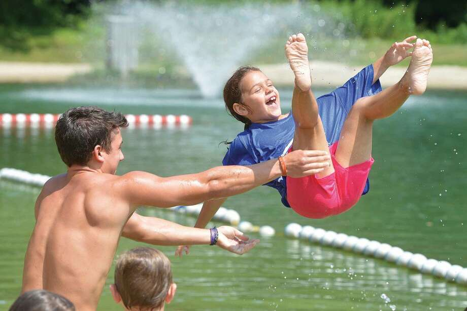 Hour Photo/Alex von Kleydorff Wilton Parks and Recs summer camp counselor Chris Ugarte plays splash down with the campers and Grace Costa, as the kids enjoy a day cooling off in the water at Merwin Meadows Park on Monday.