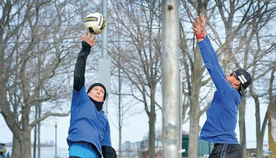 Hour Photo/Alex von Kleydorff John Anderson tries to get his hands on the ball and return a shot from Tim Epps during a game of Beach Volleyball in 40 degree weather at Calf pasture on Friday