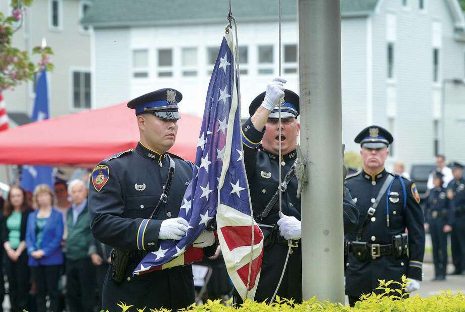 Hour Photo/Alex von Kleydorff Stamford Police Honor Guard Luis Vidal, Ryan McCallister and Chris Brown retire the colors during Peace Officers Memorial Day service at Headquaters