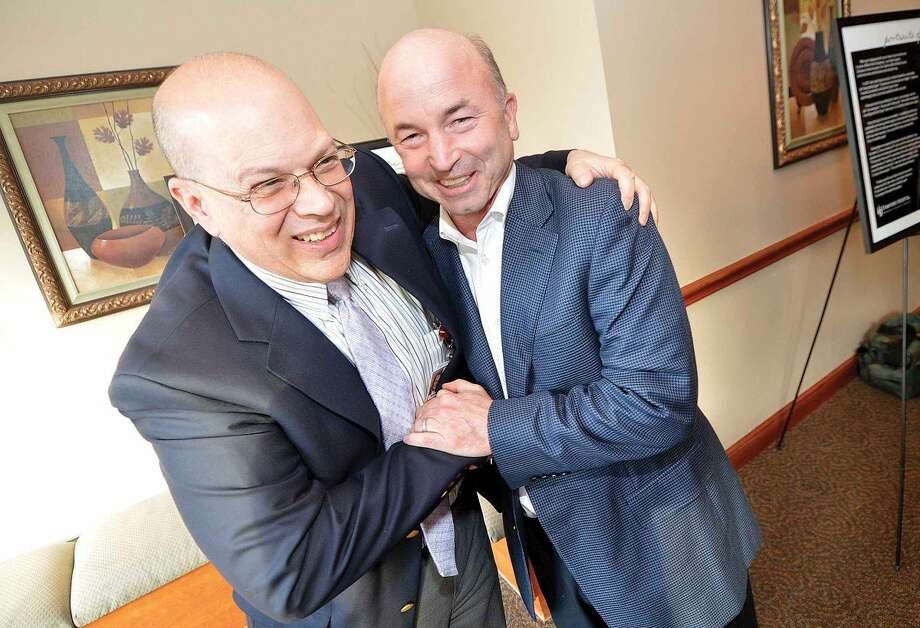 Hour Photo/Alex von Kleydorff Dr. Fank Masino, Medical Director, Bennett Cancer Center gets a hug from his patient Greg Durkin during the Portratis of Hope reception in Stamford