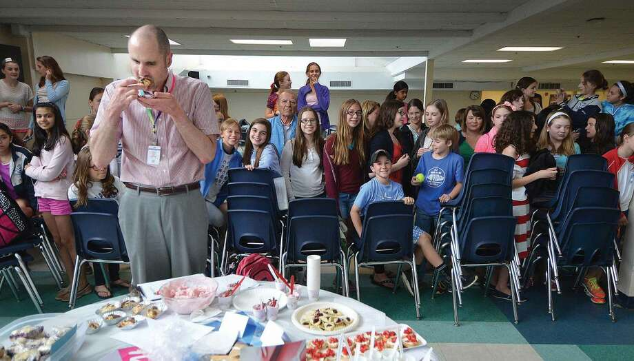 Hour Photo/Alex von Kleydorff Teacher Andrew Nicsaji trys some appetizers from Switzerland as all eyes are on him during judging at World Language week food festival at Middlebrook School