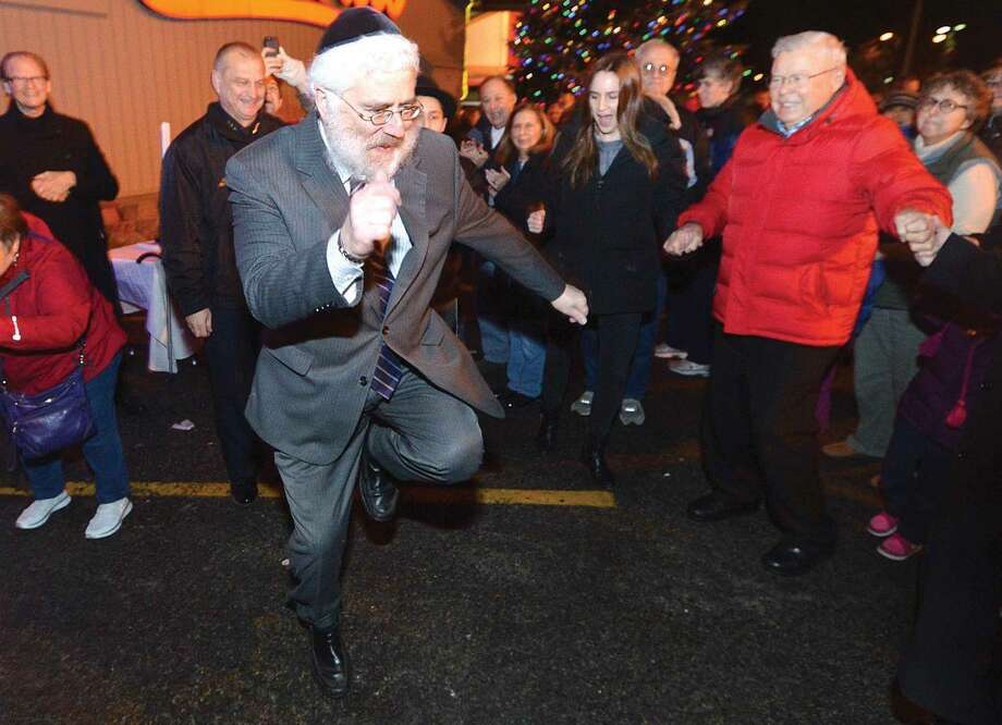 Hour Photo/Alex von Kleydorff Rabbi Jehoshua Hecht with Beth Israel in Norwalk dances to help the crowd get in the spirit of Chanukah during the lighting of the Menorah at Stew Leonard's in Norwalk