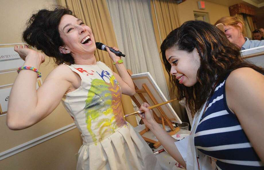 Hour Photo/Alex von Kleydorff Artist and Gallery Director and instructor for the evening, Sooo-z Mastropietro has Jenn Rodriguez along with others create a masterpice on her dress made of canvas during The Hour's Arts and Carafes event at The Hilto Garden Inn on Thursday night