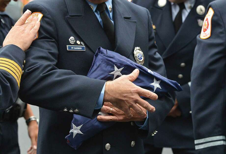 Hour Photo/Alex von Kleydorff Wilton Firefighter Pat Garber gets a touch on his shoulder patch as he grasps the American flag to Post The Colors during Wilton's 13th Annual 9-11 Memorial Service at Wilton fire Headquarters