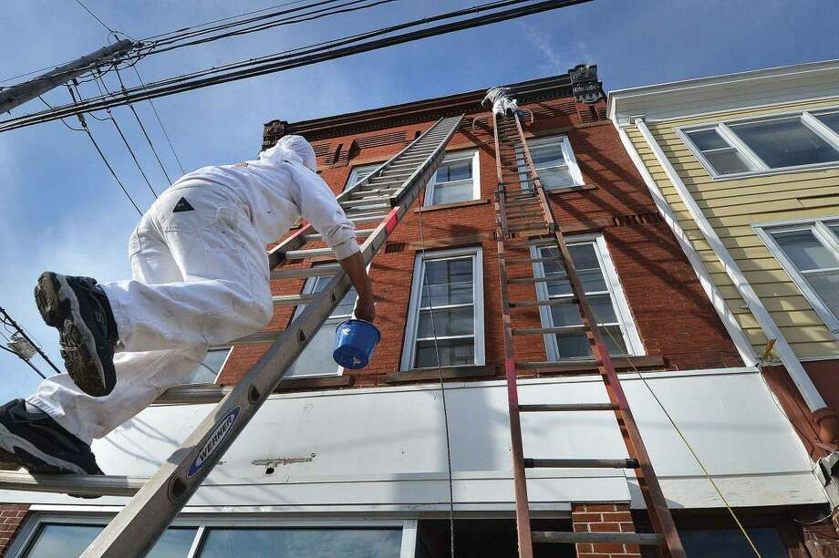 Hour Photo/Alex von Kleydorff Painters work almost 50ft high on ladders while painting the top cornice during a renovations to the facade of 203-205 Liberty Square on Monday