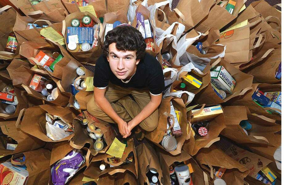 Hour Photo/Alex von Kleydorff Noah Frydman sits amidst some of the bags filled with donated food items brought in for his food drive at Congregation Beth El in Norwalk