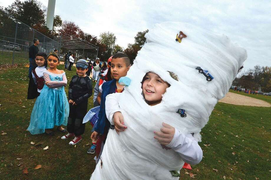 Hour Photo/Alex von Kleydorff 3rd Grader Noelia Ramos spins into the Halloween parade with cars and people caught up in her tornado costume at Brookside School