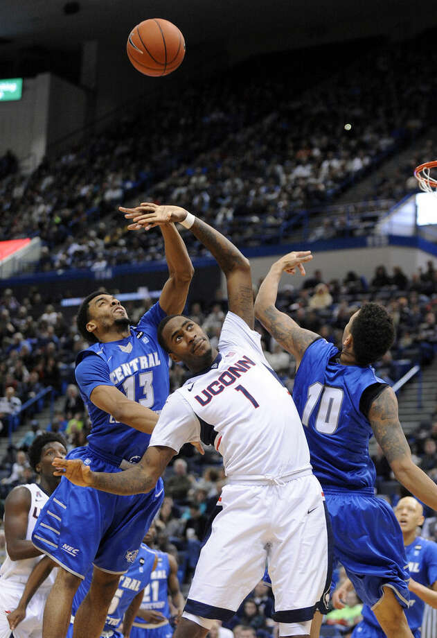 Connecticut's Phillip Nolan (1) fights for a rebound with Central Connecticut State's Greg Andrade, left, and Corey Barrett during the first half of an NCAA college basketball game in Hartford, Conn., on Sunday, Dec. 28, 2014. (AP Photo/Fred Beckham)