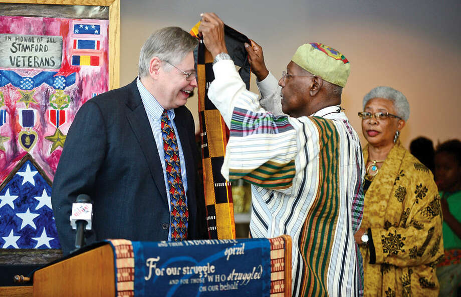 Hour photo / Erik Trautmann Stamford mayor david martin is presented with a traditional african Kente stole from Phillip McKain during the city's 20th annual Kwanzaa celebration Tuesday at the Stamford Government Center.