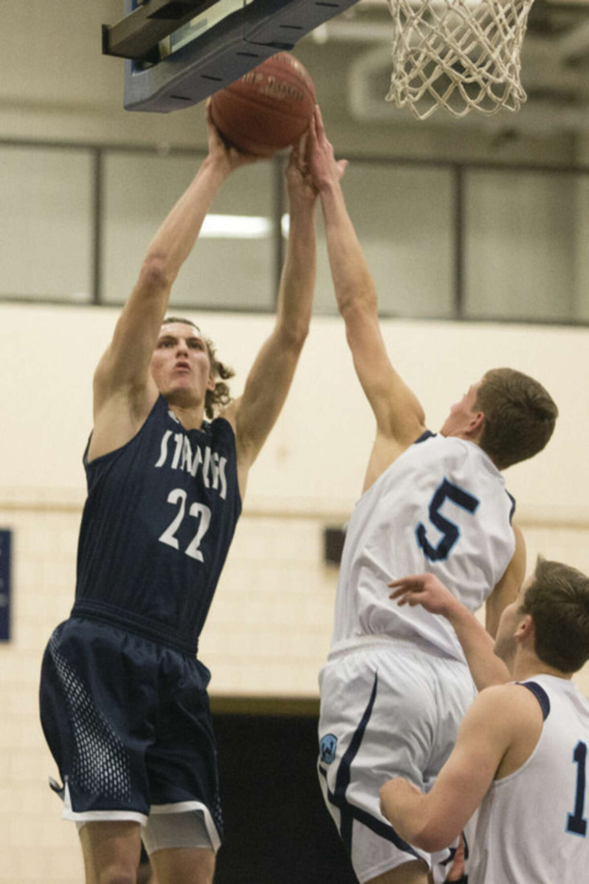 Hour photo/Chris Palermo Staples' Nic Esposito puts up a shot during Monday night's game against Wilton, as the Warriors' Miles Elmasry contests.