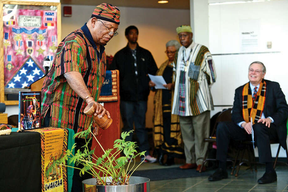 Hour photo / Erik Trautmann The Baba Thomas Bradford offers up libation during the Stamford's 20th annual Kwanzaa celebration Tuesday at the Stamford Government Center.
