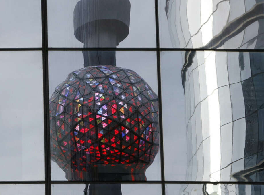 Workers light the Waterford crystal ball during a test for the New Year's Eve celebration atop One Times Square in New York, Tuesday, Dec. 30, 2014. The ball, which is 12 feet in diameter and weighs 11,875 pounds, is decorated with 2,688 Waterford crystals and illuminated by 32,256 LED lights. (AP Photo/Kathy Willens)