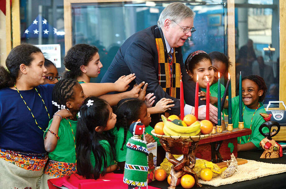Hour photo / Erik Trautmann Stamford Mayor David Martin lights candles with children from the community during the city's 20th annual Kwanzaa celebration Tuesday at the Stamford Government Center.