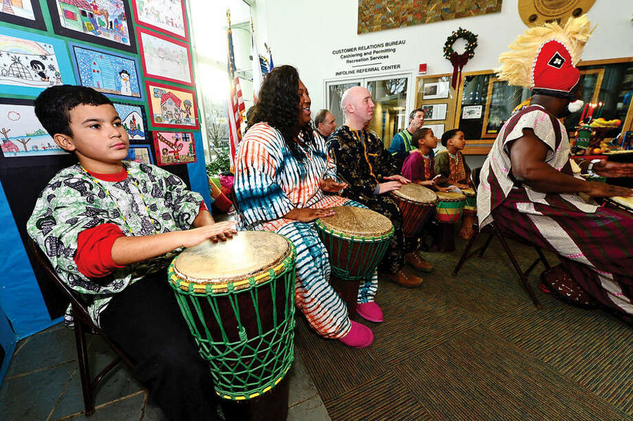 Hour photo / Erik Trautmann Jeremiah Ortiz, left, plays with the Infinite Roots drum troupe during the city's 20th annual Kwanzaa celebration Tuesday at the Stamford Government Center.