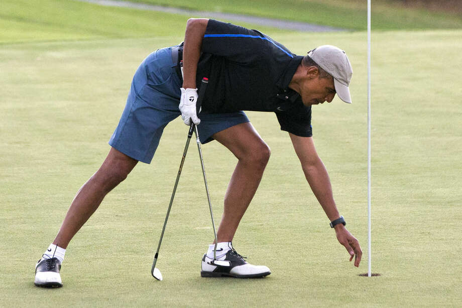 President Barack Obama reaches for his ball after making par while golfing with Bobby Titcomb, Greg Orme, and Mike Ramos on Monday, Dec. 29, 2014, on the 18th hole of the Mid Pacific Country Club in Kailua, Hawaii during the Obama family vacation. (AP Photo/Jacquelyn Martin)