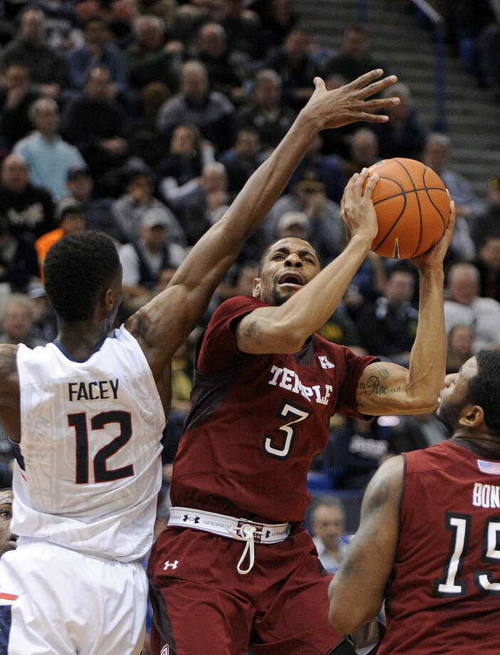 Temple's Jesse Morgan (3) drives past Connecticut's Kentan Facey (12) during the first half of an NCAA college basketball game in Hartford, Conn., on Wednesday, Dec. 31, 2014. (AP Photo/Fred Beckham)
