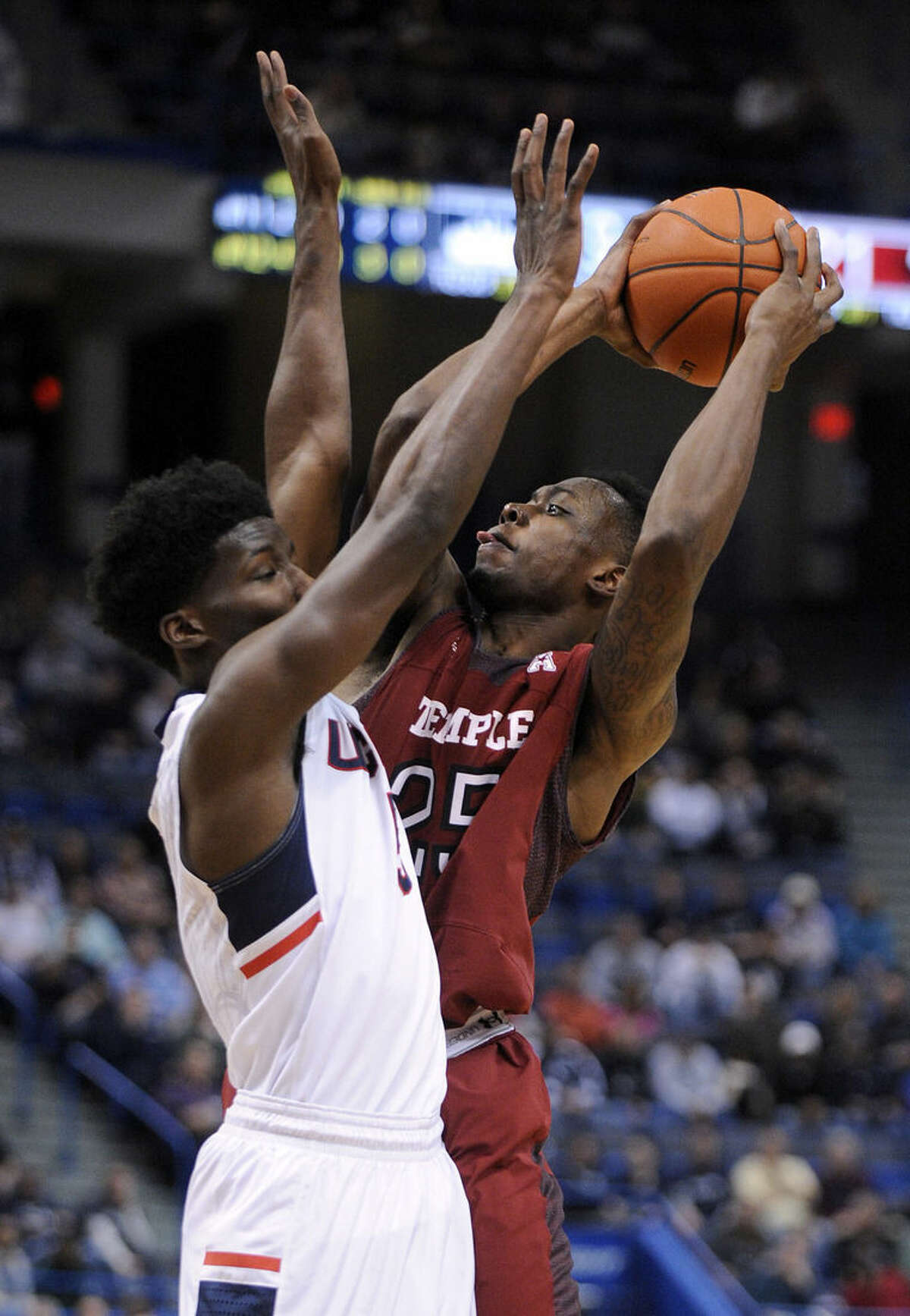 Temple's Quenton DeCosey (25) shoots over Connecticut's Daniel Hamilton (5) during the first half of an NCAA college basketball game in Hartford, Conn., on Wednesday, Dec. 31, 2014. (AP Photo/Fred Beckham)