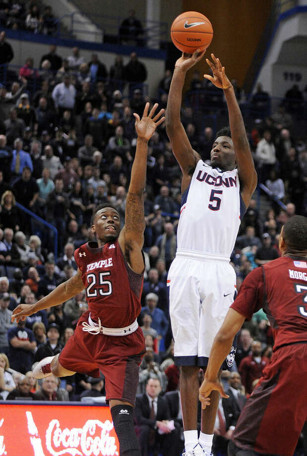 Connecticut's Daniel Hamilton (5) is fouled by Temple's Quenton DeCosey (25) late in the overtime of his team's 57-53 loss in an NCAA college basketball game in Hartford, Conn., on Wednesday, Dec. 31, 2014. (AP Photo/Fred Beckham)