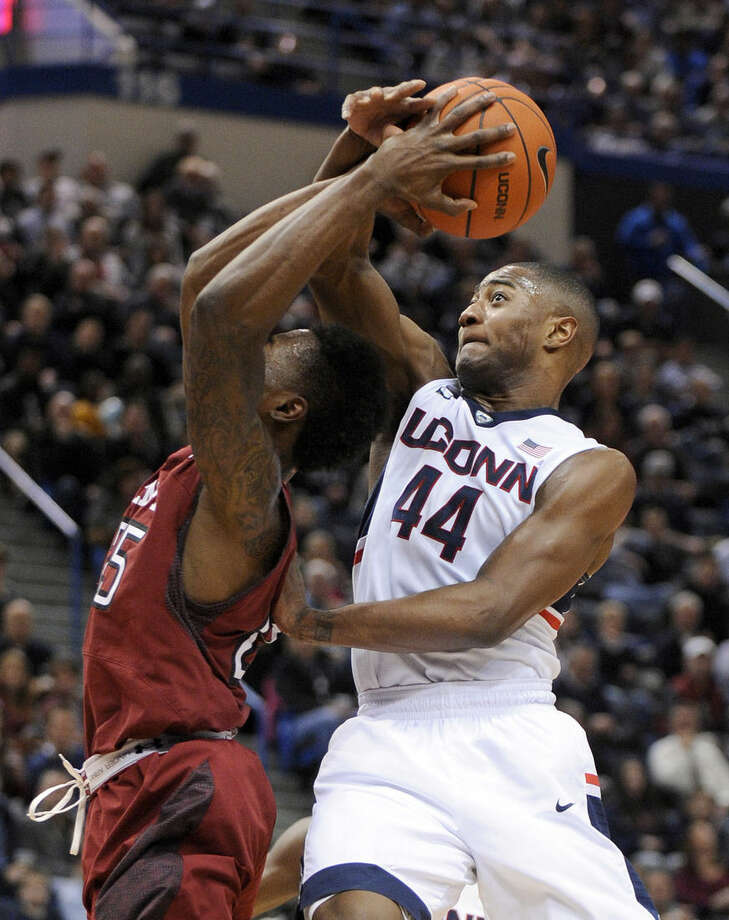 Connecticut's Rodney Purvis (44) fouls Temple's Quenton DeCosey (25) during the first half of an NCAA college basketball game in Hartford, Conn., on Wednesday, Dec. 31, 2014. (AP Photo/Fred Beckham)