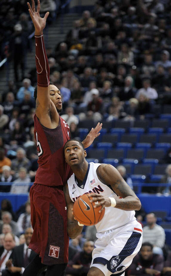 Connecticut's Phillip Nolan (1) drives past Temple's Devontae Watson (23) during the first half of an NCAA college basketball game in Hartford, Conn., on Wednesday, Dec. 31, 2014. (AP Photo/Fred Beckham)
