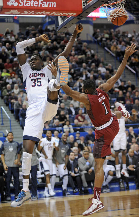 Connecticut's Amida Brimah (35) is fouled by Temple's Josh Brown (1) late in the second half of Temple's 57-53 overtime victory in an NCAA college basketball game in Hartford, Conn., Wednesday, Dec. 31, 2014. (AP Photo/Fred Beckham)