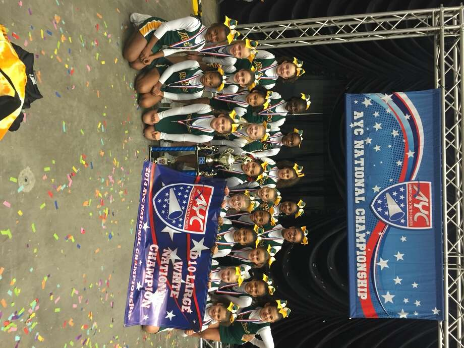 The U-10 Norwalk Packers cheerleaders with their National Championship banner and trophy after winning second consecutive National Championship Sunday night.