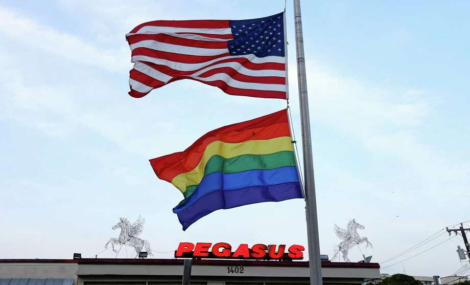 An American and rainbow flags fly at half staff outside Pegasus San Antonio, Sunday June 12, 2016 in response to the Orlando, Fla. shooting. Photo: Edward A. Ornelas, Staff / San Antonio Express-News / © 2016 San Antonio Express-News