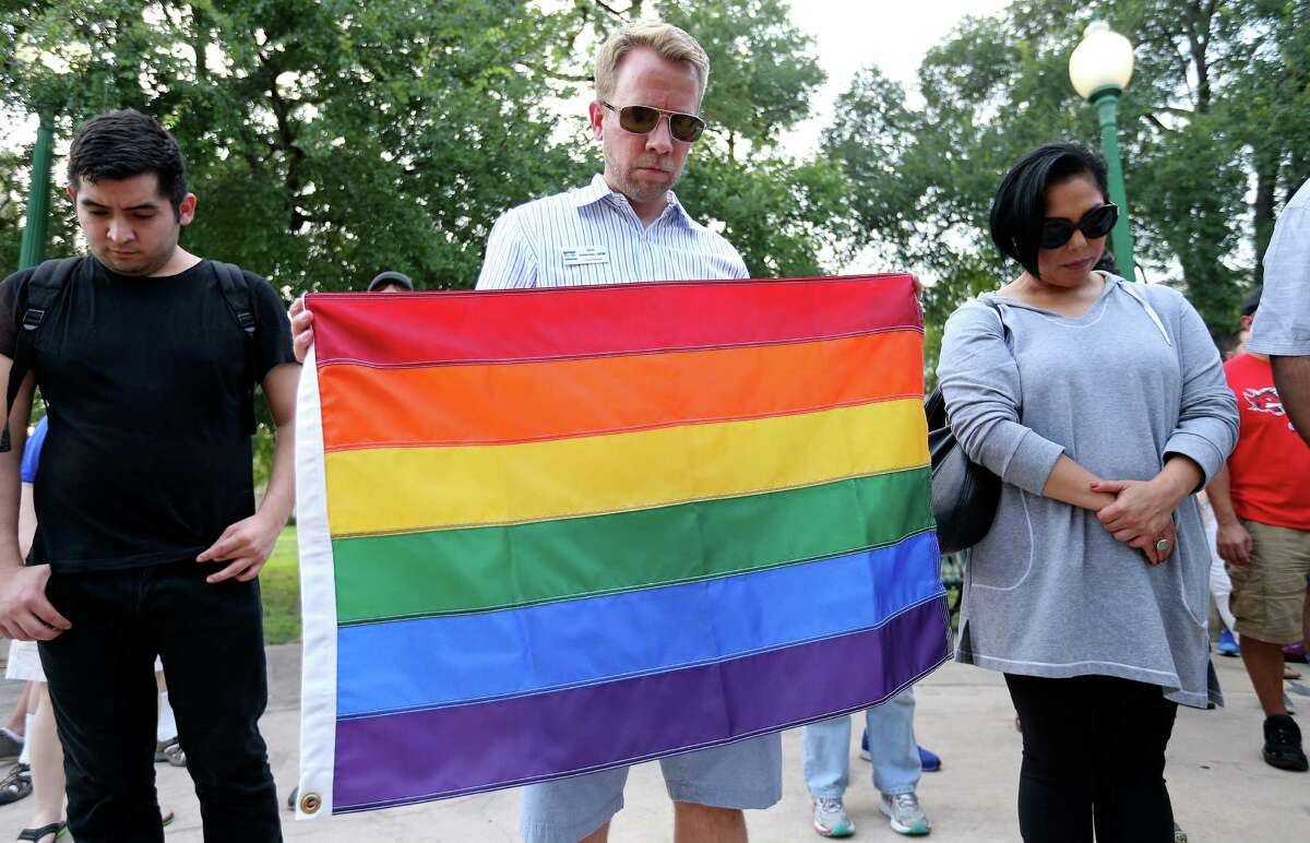 Pride Center San Antonio Board Member Brian Halderman (center) and others pray during a vigil for the Orlando, Fla. shooting held Sunday June 12, 2016 at Crockett Park. About 300 people attended the vigil.