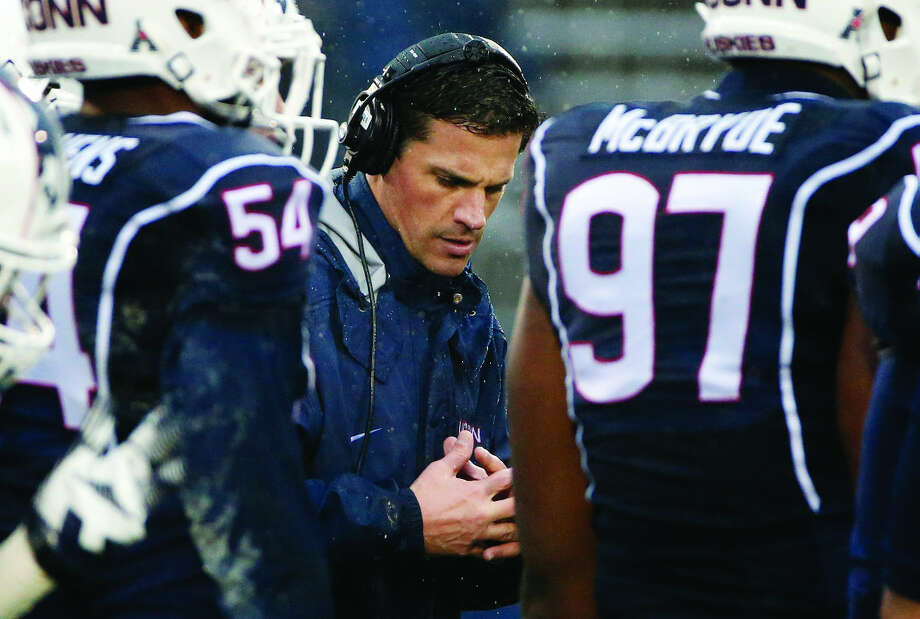 Connecticut head coach Bob Diaco, center, with his team during the fourth quarter of an NCAA college football game in East Hartford, Conn., Saturday, Dec. 6, 2014. Southern Methodist won 27-20. (AP Photo/Michael Dwyer)